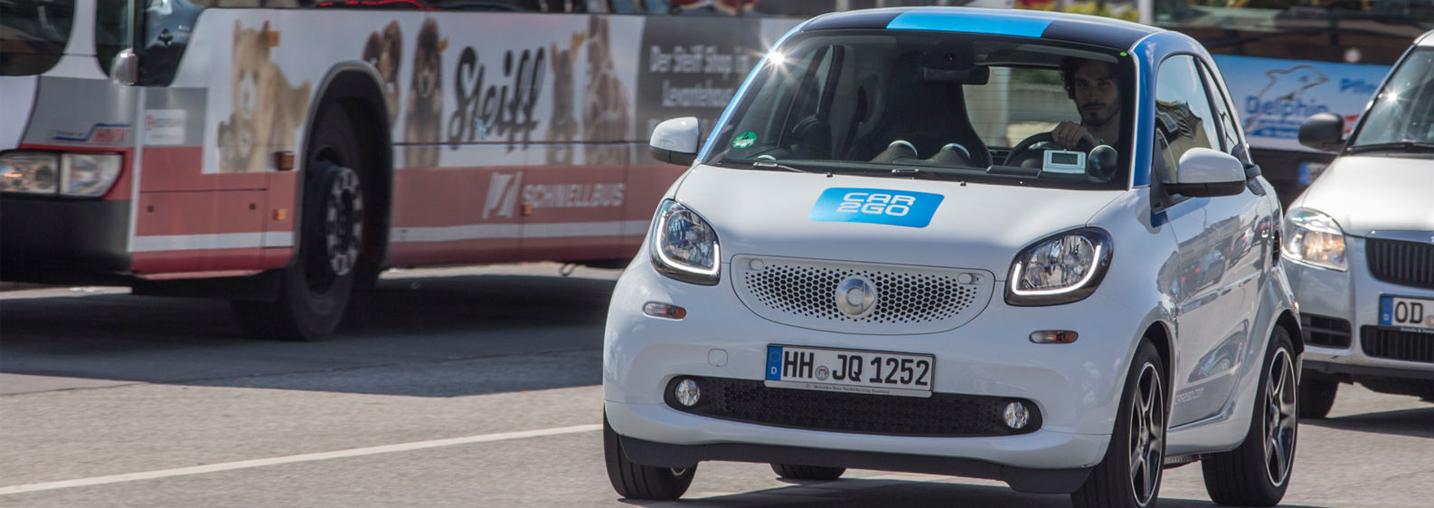 Der neue Smart fortwo von car2go auf der Straße mit einem Bus im Hintergrund