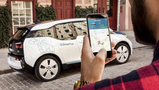 Ein junger Mann öffnet DriveNow BMW i3 mit dem Smartphone