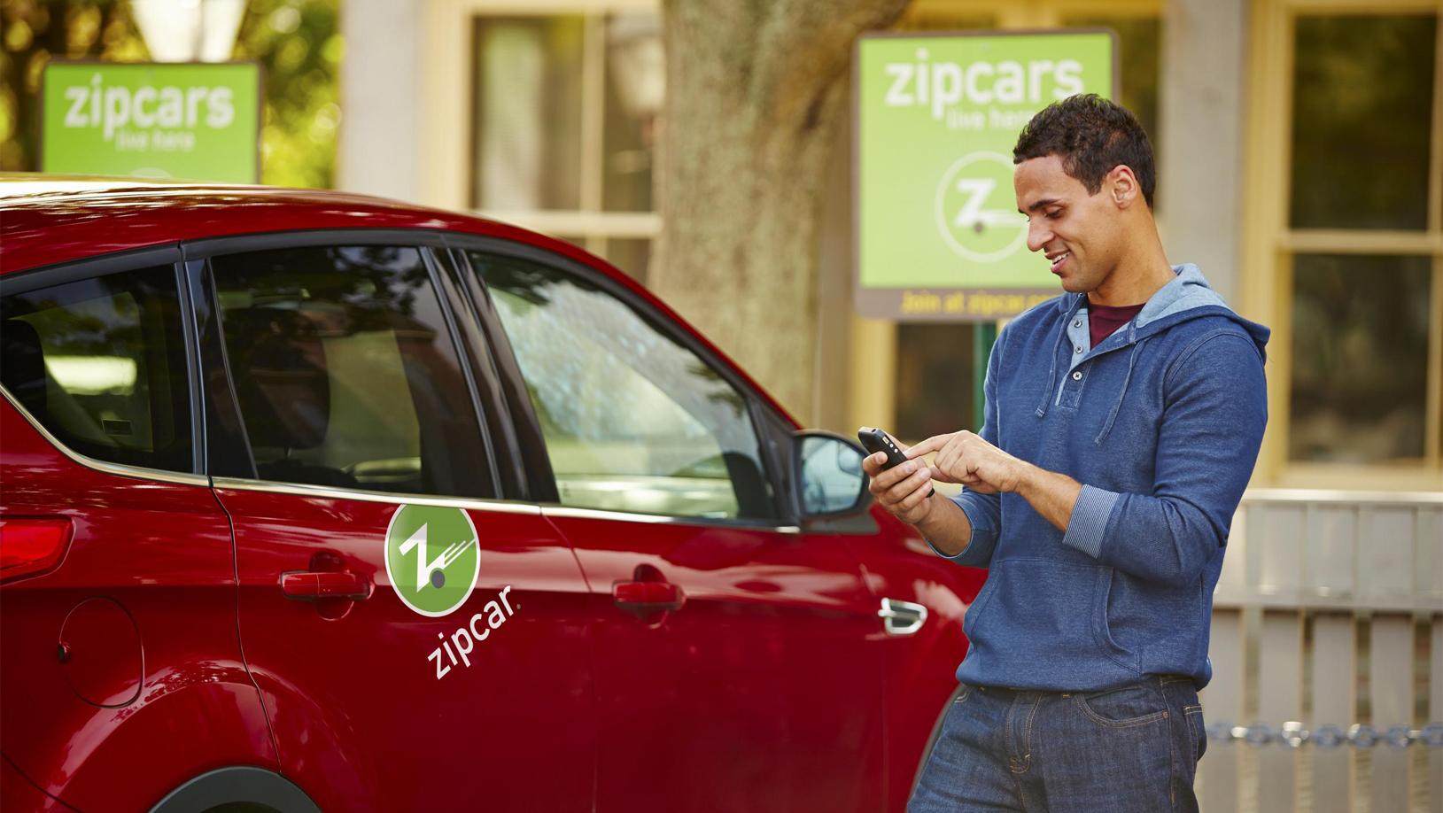 Zipcar Kunde steht vor einem Ford Focus